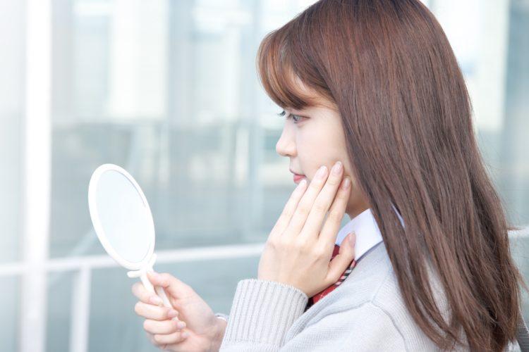 水光注射のダウンタイムが気になり鏡を見る女性