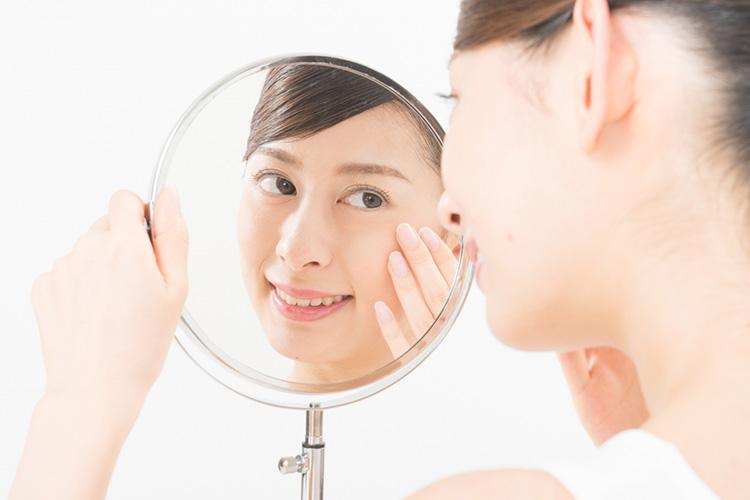 切らない眼瞼下垂手術後、鏡で仕上りを確認する女性